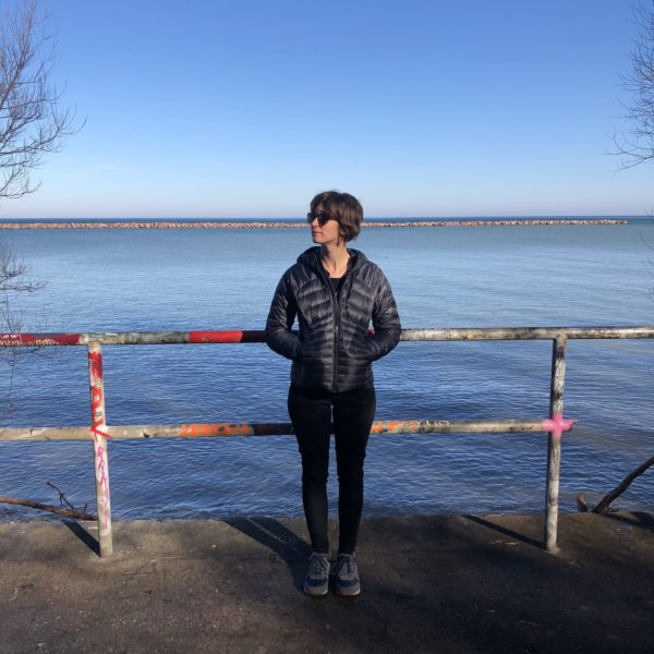 Mandi standing with her hands in her pocket up against a graffitied fence next. Lake Michigan and the break wall are in the background.
