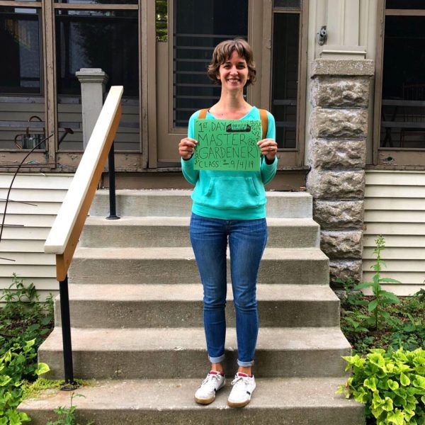 """Mandi standing on her front porch with her backpack on. She's holding a sign that reads """"1st Day Master Gardener Class - 9/4/19""""."""