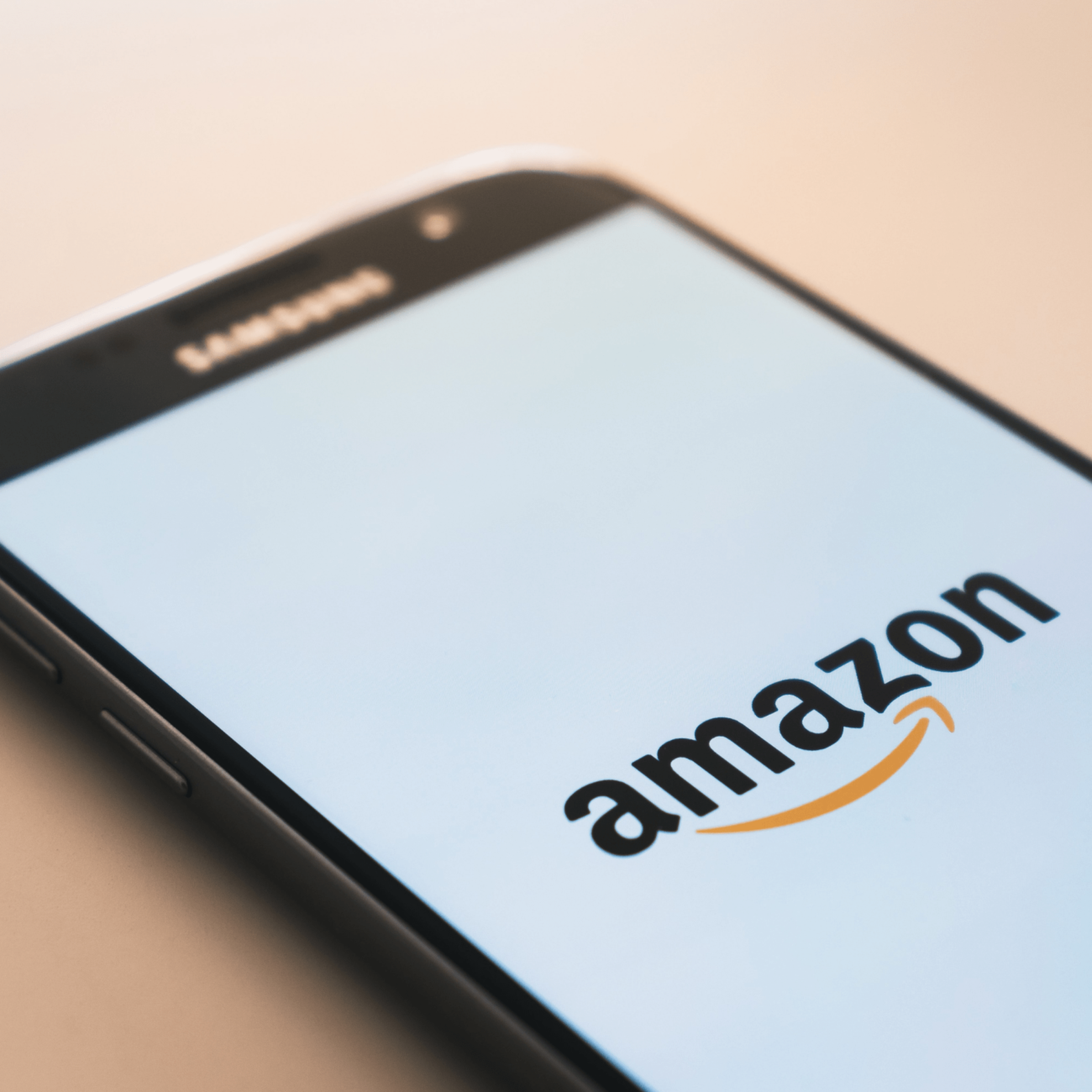 Smartphone sitting on a table with the Amazon logo on its screen.