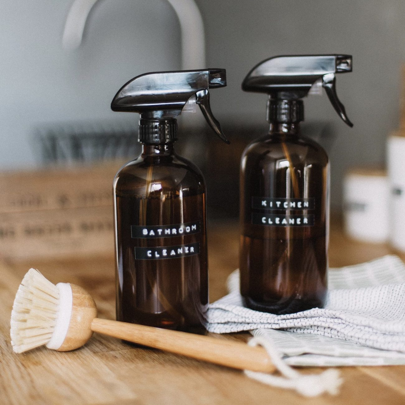 Two glass cleaning bottles sitting next to a wooden scrub brush and towels on a counter.