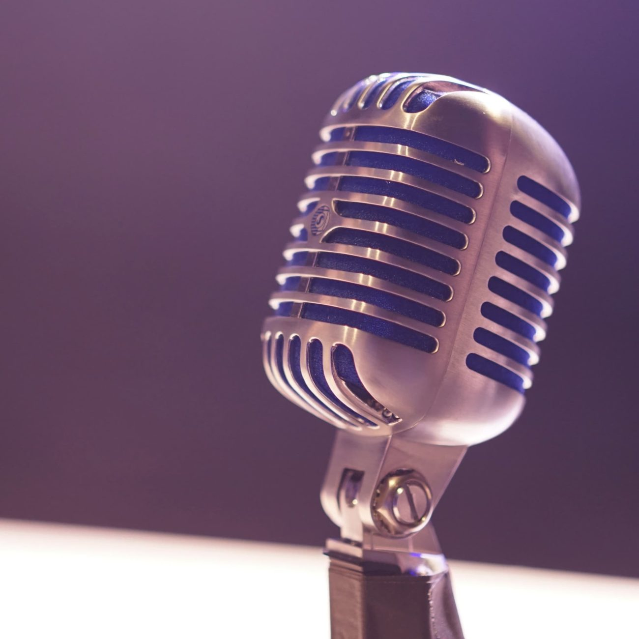 Close up of an old-fashioned radio microphone in front of a purple background.