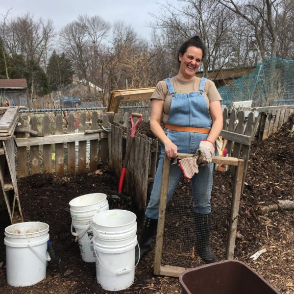 Renee from Kompost Kids standing in front of a pile of compost. She's standing next to three buckets and holding a compost screening tool.
