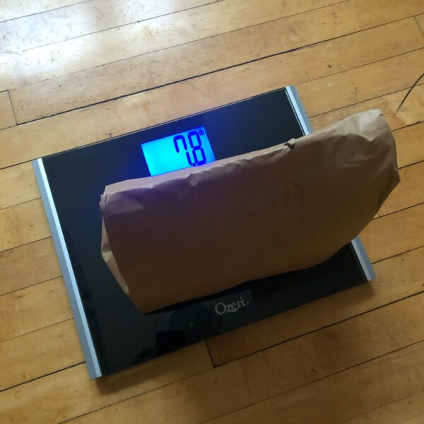Half full brown paper bag sitting on bathroom scale. Scale reads 7.8lbs.